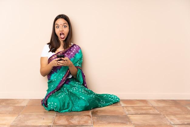 Молодая индийская женщина сидит на полу удивлен и отправив сообщение