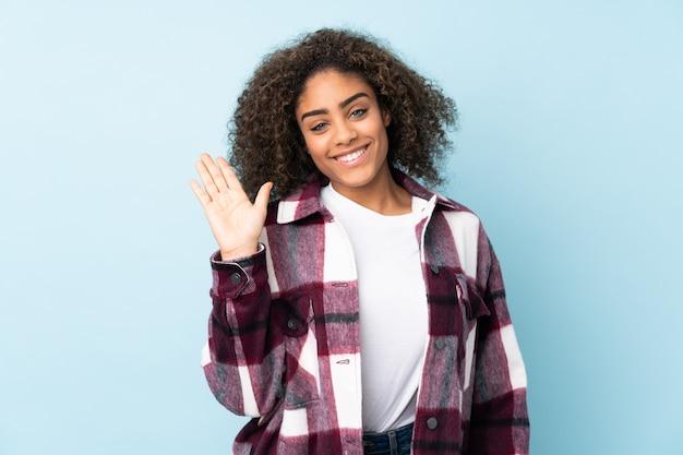 幸せな表情で手で敬礼青い壁に分離された若い女性