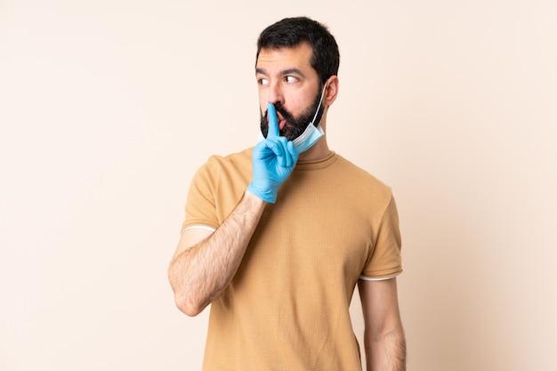 口を開けて指を置く沈黙のジェスチャーの兆しを見せ分離の壁にマスクと手袋で保護するひげを持つ白人男