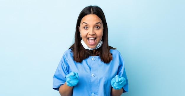 Женщина-хирург над синей стеной празднует победу в позиции победителя