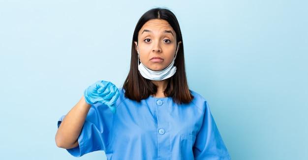 否定的な表現で親指を示す青い壁の上の外科医の女性