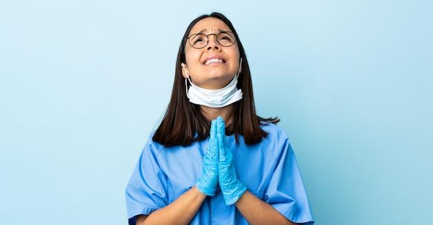 Женщина хирург над синей стеной держит ладонь вместе.