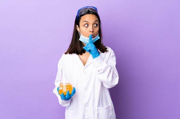 科学者の女性が口に指を入れて沈黙のジェスチャーの兆候を示すコロナウイルス病を治療するワクチンを調査