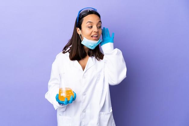 Женщина-ученая, исследующая вакцину для лечения коронавирусной болезни, слушая что-то, положив руку на ухо