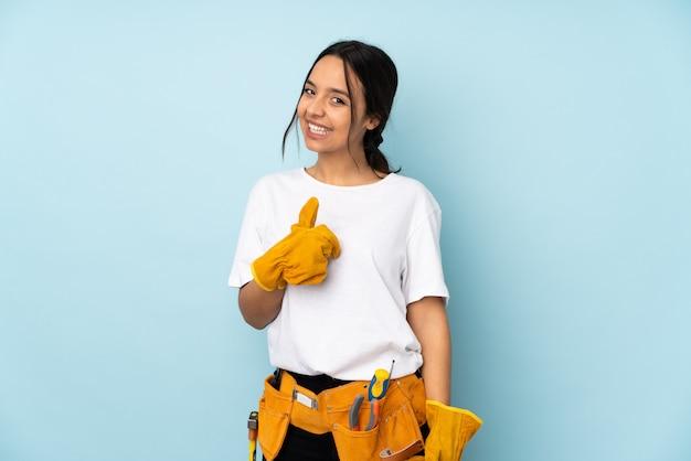 親指ジェスチャーを与える青い壁に分離された若い電気技師女性