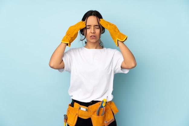 頭痛で青い壁に分離された若い電気技師女性