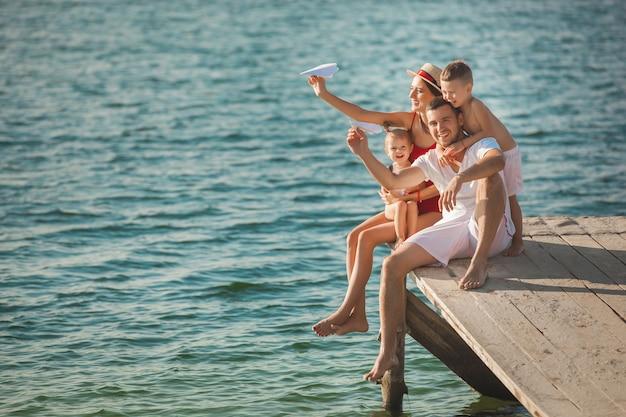 楽しい水の近くの桟橋で幸せな陽気な家族。親と遊ぶ愛らしい子供たち