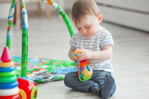屋内で遊ぶかわいい子。かわいい幼児男の子