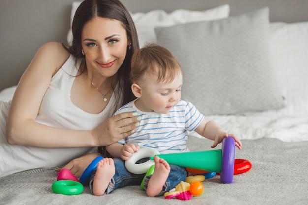 若い可愛い母親が幼い息子と遊ぶ。屋内で小さな赤ちゃんの息子と楽しんで陽気な家族
