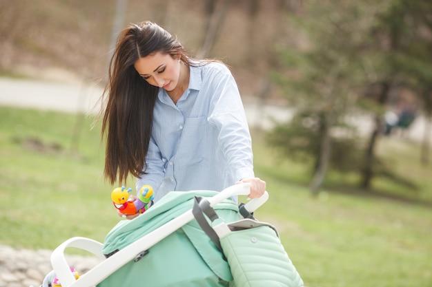 Молодая жизнерадостная мать гуляет с ребенком в коляске