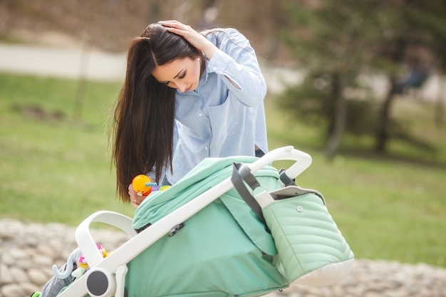 屋外で彼女の小さな赤ちゃんを落ち着かせようとしている若い母親