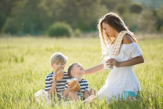 屋外で彼女の子供と有機の新鮮な牛乳を飲む若い母親
