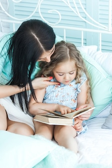 おやすみの話を子供に読んでいる愛情深い母親