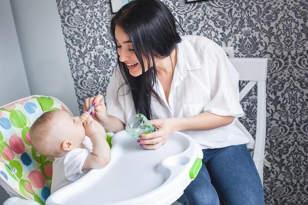 Молодая мать кормит своего маленького ребенка