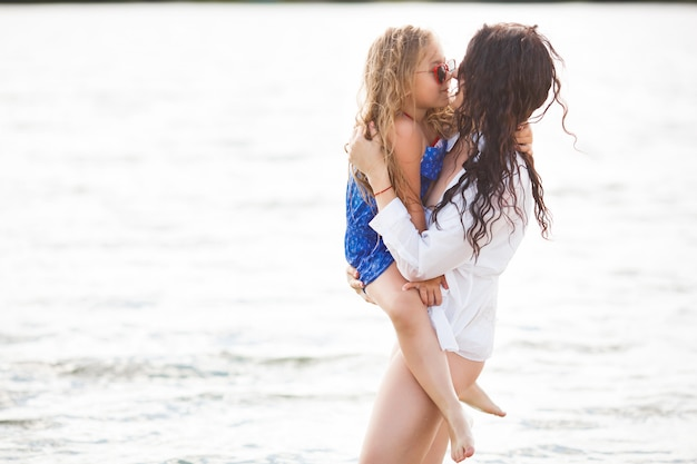 楽しいビーチで陽気な女の子。若い母親と海岸線に彼女の小さなかわいい娘。