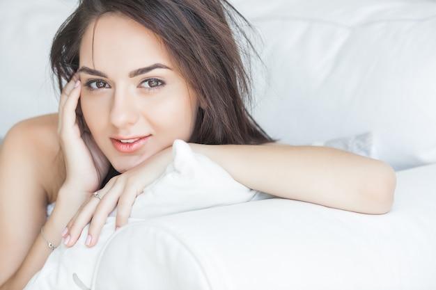 Привлекательный портрет молодой женщины крупным планом. женщина в помещении. красивая женщина в постели.