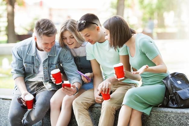 若者がスマートフォンで入力します。携帯電話で見ている友人のグループ。若者とデジタル技術。