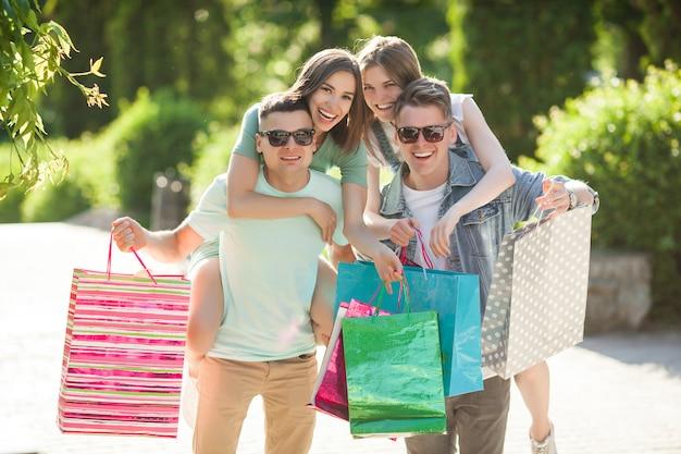 買い物をする若い魅力的な人々のグループ。屋外で買い物袋を押しながら笑顔の友人。一緒に陽気な友達。