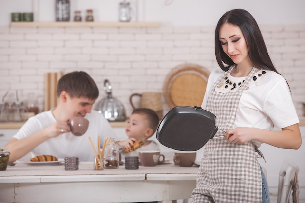 キッチンで彼女の家族の前に立っている若い母親。夕食や朝食を食べて幸せな家族。彼女の夫と小さな赤ちゃんの夕食を作る女性。