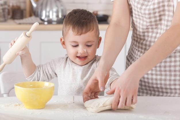 生地を準備する女性。ダウと小麦粉で女性の手のクローズアップ。イタリア料理の準備プロセス。