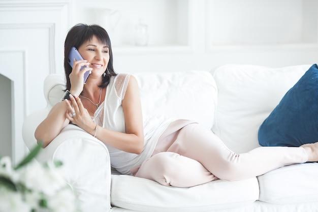 Привлекательная зрелая женщина разговаривает по мобильному телефону и делает селфи. взрослая леди в помещении держит смартфон.