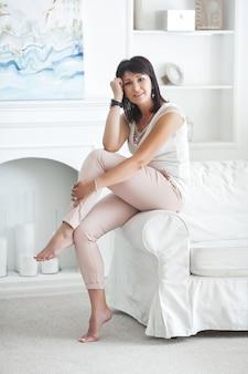 Привлекательная взрослая женщина, сидя на диване в помещении. красивая женщина среднего возраста дома.