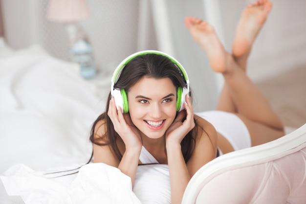 音楽を聴く陽気な若い女性。イヤホンを着て美しい少女