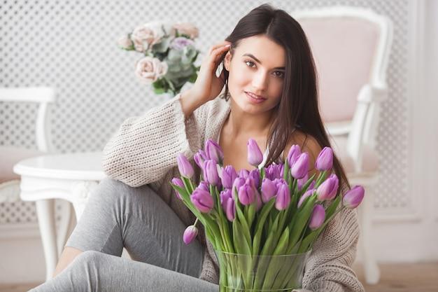 花を保持している美しい若い女性の肖像画を間近します。チューリップと魅力的な女性