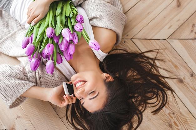 Веселая молодая женщина разговаривает по телефону и держит цветы. красивая дама с тюльпанами