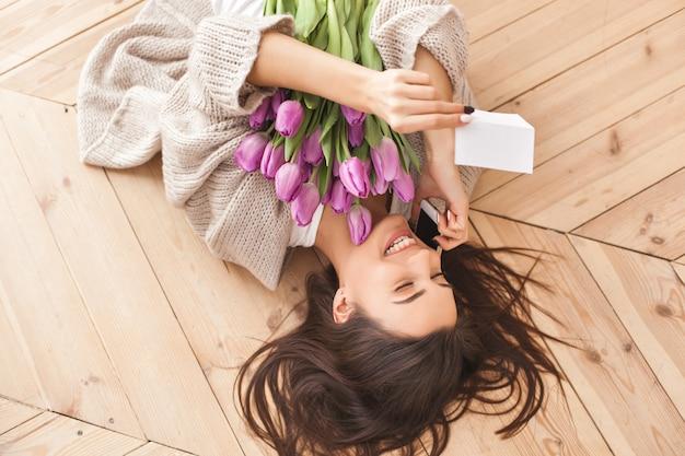 花の花束を保持している若い魅力的な女性