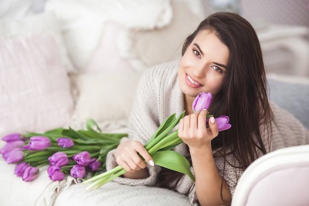 花を保持している若い魅力的な女性。ベッドの上に横たわるチューリップと美しい女性