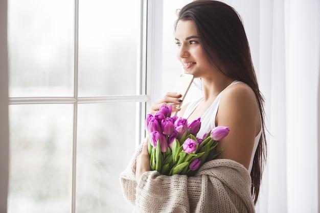 花と美しい若い女性の肖像画。魅力的な女の子持株チューリップ