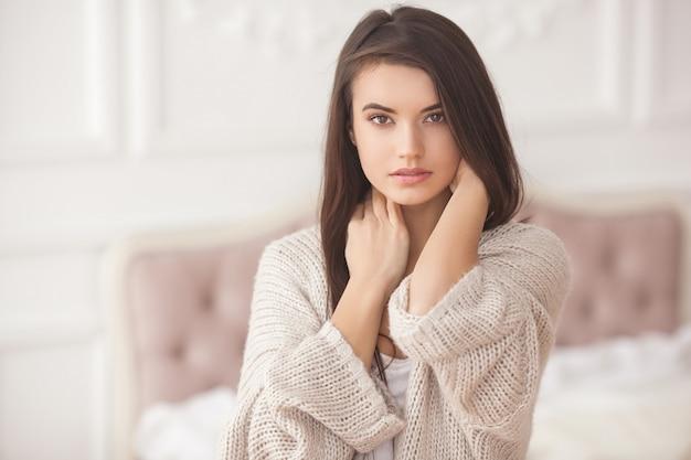 屋内で美しい若い女性の肖像画。かわいい女の子をクローズアップの肖像画