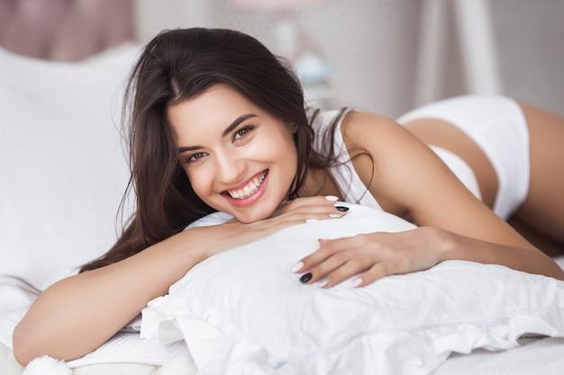 ベッドで非常に美しい女性。寝室の若い魅力的な女性の肖像画