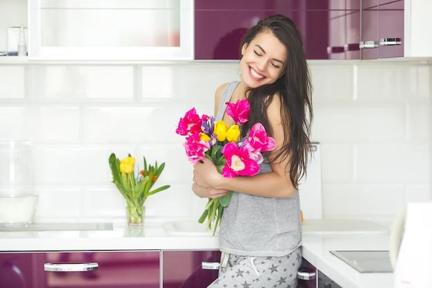 花を保持している若い魅力的な女性。チューリップとキッチンの女性。家庭の台所に立っている朝の主婦。