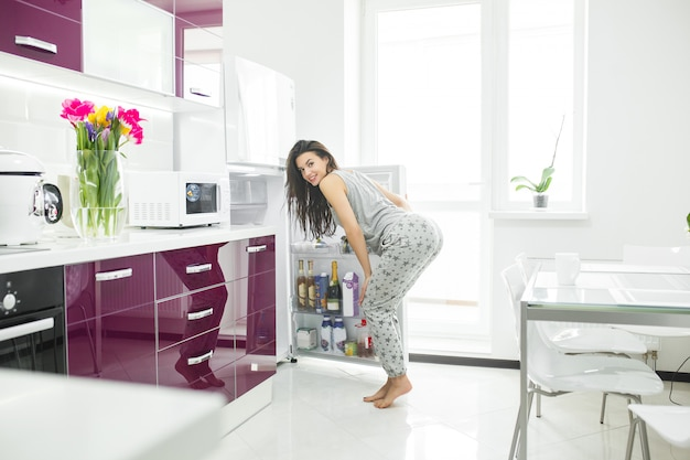 ダイエット詐欺師。冷蔵庫の近くの台所の女性。女性は食べたいです。朝の空腹の女性。