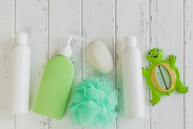 木製のテーブルのシャンプーボトル。ベビーバスアクセサリー。子供用トイレ。バスルームチューブ、香油、海塩、石鹸。