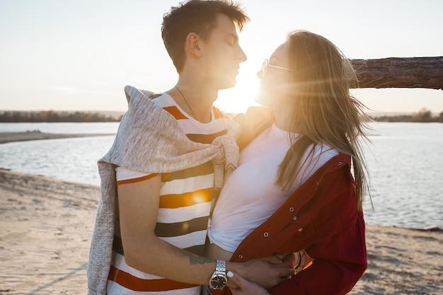 ビーチで夕日に若いカップルを愛しています。愛。男と女のキスと夏を受け入れます。