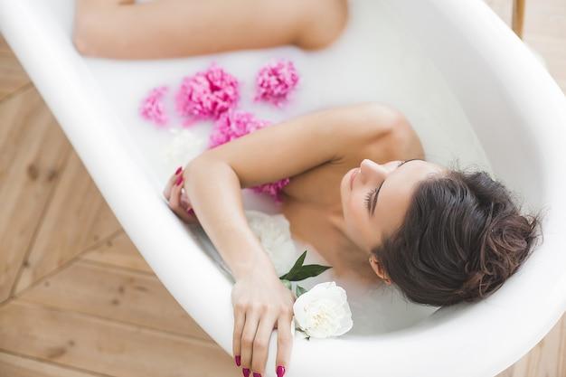 花とミルクで若い美しい女性入浴