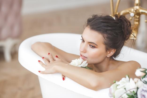 Молодая красивая женщина, принимая ванну с цветами и молоком