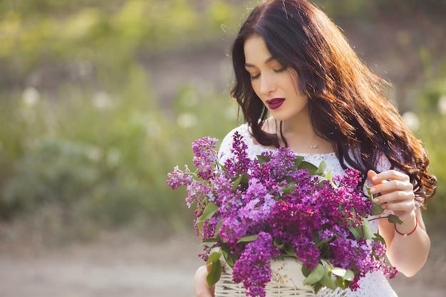 屋外の美しい少女。ライラックの花束を持つかなり若い女性。花を持つ女性をクローズアップ