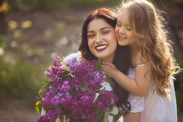 若い美しい母親と一緒に楽しんで小さな娘。かわいいお母さんとかわいい女の子屋外。陽気な家族一緒に