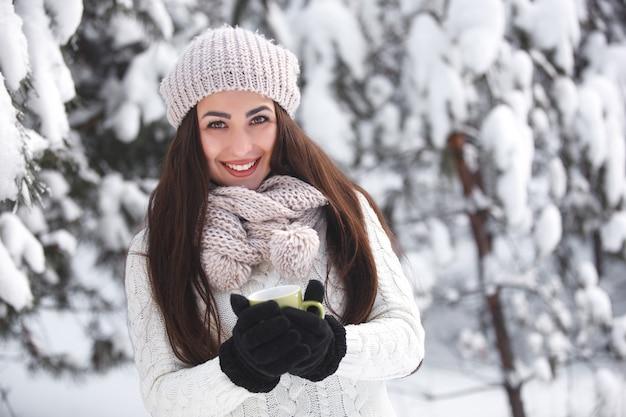 Красивая девушка в лесу зимой с чаем.