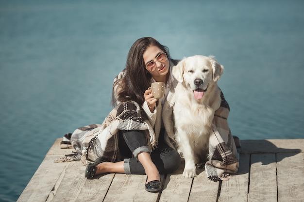 彼女の犬と桟橋に座っている若い魅力的な女性。屋外の親友