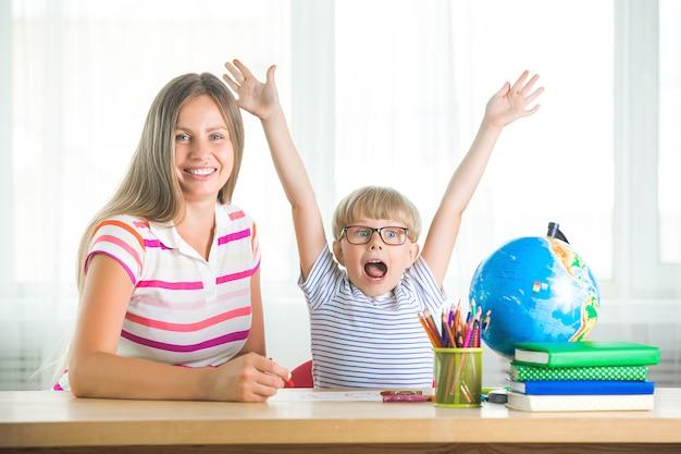 Милый ребенок учится урок с матерью. семья вместе делать домашнее задание. мот объяснила своему маленькому школьнику, как выполнить задание.