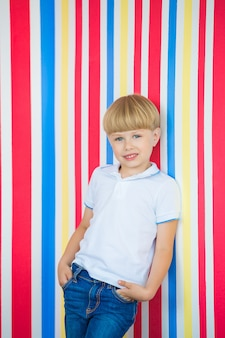 かわいい子はカラフルな肖像画を閉じます。壁の近くに立っている愛らしい少年。