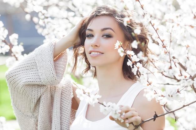春に若い美しい女性の肖像画を閉じます。花を持つ魅力的な若い女の子。春のメイクアップモデル。
