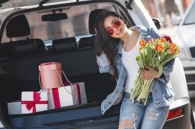 花を保持している車の中で非常に美しい女性