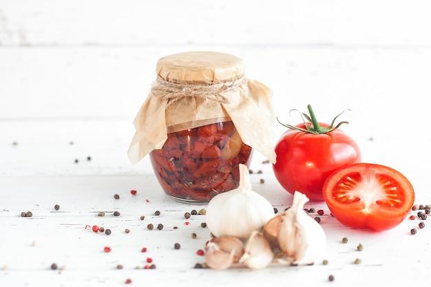 瓶の中のトマト。自家製の天日干しトマト。一時的な閉鎖。夏と秋の缶詰。スパイスと野菜を節約します。