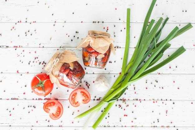 天日干しトマトのトップビュー。自家製の保全と瓶のフラットレイアウトショット。トマトと一緒に保存します。ピザ用のイタリアのスパイス。